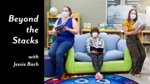 Photo of three librarians wearing masks due to the pandemic, sitting in a library and holding books.