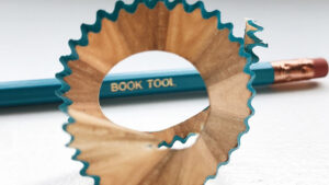 """A pencil that says """"Book Tool"""" on it"""