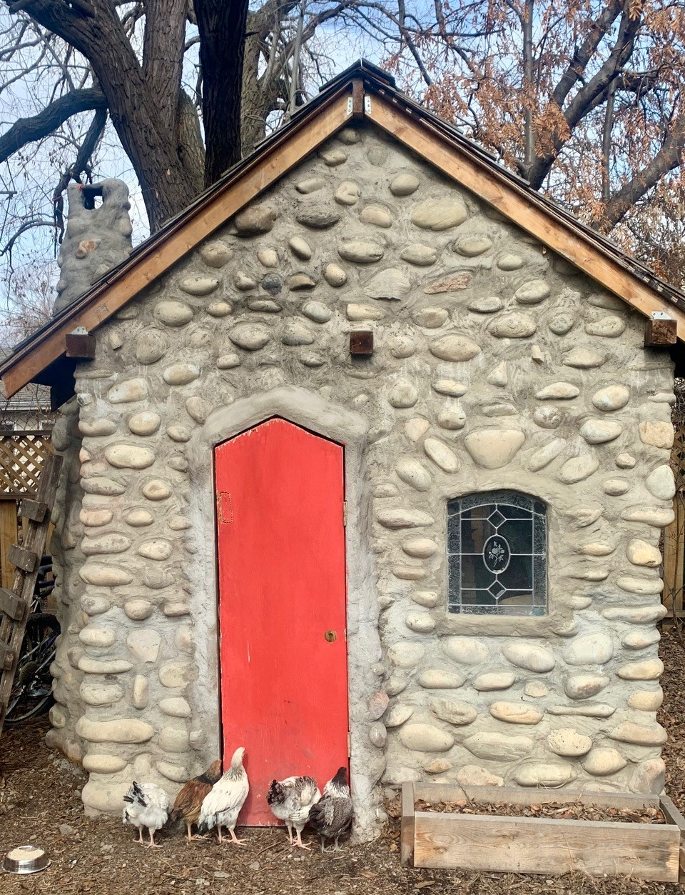 A stone shack with a teeny window and a narrow red door, with chickens standing outside